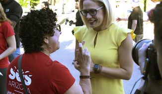 A supporter crosses her fingers as she talks with Democratic U.S. Senate candidate Kyrsten Sinema, at a get-out-the-vote event at the Arizona Education Association headquarters in Phoenix,  Saturday, Nov. 3, 2018. Sinema is facing Republican Martha McSally in the race to replace Republican Sen. Jeff Flake, who is retiring.  (AP Photo/Bob Christie)