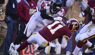 Atlanta Falcons cornerback Brian Poole (34) stops Washington Redskins quarterback Alex Smith's (11) long run during the first half of an NFL football game Sunday, Nov. 4, 2018 in Landover, Md. (AP Photo/Susan Walsh)