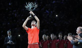 Karen Khachanov of Russia raises the trophy after defeating Novak Djokovic of Serbia in their final match of the Paris Masters tennis tournament at the Bercy Arena in Paris, France, Sunday, Nov. 4, 2018. (AP Photo/Michel Euler)