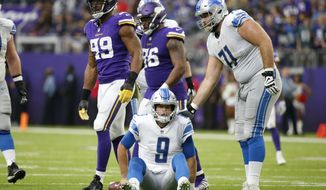 Detroit Lions quarterback Matthew Stafford (9) sits on the field after getting sacked by Minnesota Vikings defensive end Danielle Hunter (99) during the first half of an NFL football game, Sunday, Nov. 4, 2018, in Minneapolis. (AP Photo/Bruce Kluckhohn)