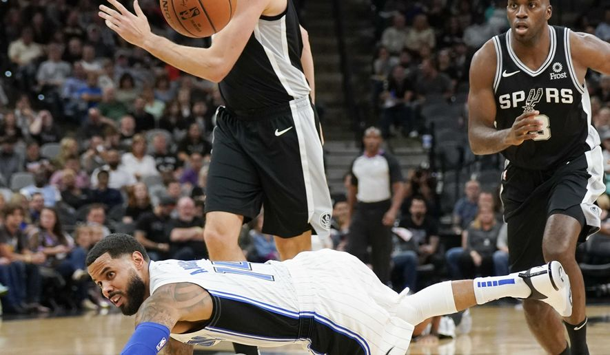 Orlando Magic's D.J. Augustin, front, falls after being fouled by San Antonio Spurs' Pau Gasol, left, during the first half of an NBA basketball game, Sunday, Nov. 4, 2018, in San Antonio. (AP Photo/Darren Abate)