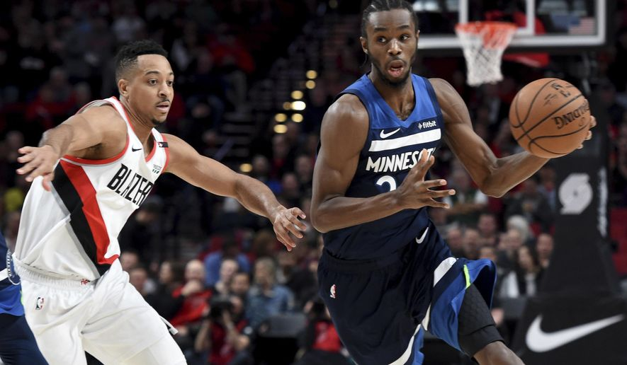 Minnesota Timberwolves forward Andrew Wiggins, right, tries to get past Portland Trail Blazers guard CJ McCollum, left, during the first quarter of an NBA basketball game in Portland, Ore., Sunday, Nov. 4, 2018. (AP Photo/Steve Dykes)
