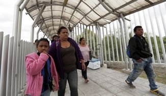 FILE- In this Saturday, Nov. 3, 2018, file photo immigrants seeking asylum in the United States walk off of the the International Bridge in Reynosa, Mexico. Asylum seekers already camping at border crossings worry that how the Trump administration responds to the caravan of some 4,000 Central American migrants and three much smaller ones hundreds of miles behind it could leave them shut out. (AP Photo/Eric Gay, File)