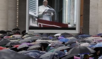 The image of Pope Francis is projected on a giant screen during the Angelus noon prayer he delivered from his studio's window overlooking St. Peter's Square at the Vatican, Sunday, Nov. 4, 2018. (AP Photo/Gregorio Borgia)