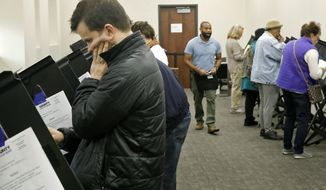 Andrew Shinn, from University City, votes during absentee voting on Monday, Nov. 5, 2018, at the St. Louis County Board of Elections in St. Ann, Mo. (J.B. Forbes/St. Louis Post-Dispatch via AP)