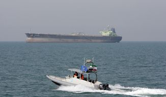 In this July 2, 2012, file photo, an Iranian Revolutionary Guard speedboat moves in the Persian Gulf while an oil tanker is seen in background. (AP Photo/Vahid Salemi, File)