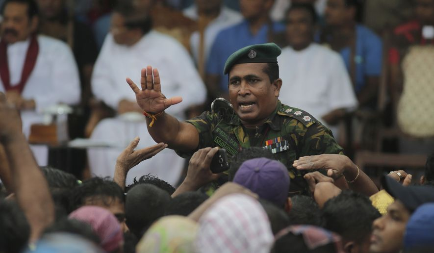 A Sri Lankan police officer tries to control supporters of Sri Lankan President Maithripala Sirisena and his newly appointed prime minister, Mahinda Rajapaksa, during a rally Monday outside the parliamentary complex in Colombo. (Associated Press)