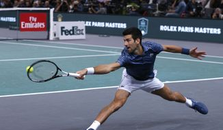 Novak Djokovic of Serbia stretches for the ball return it to Karen Khachanov of Russia during their final match of the Paris Masters tennis tournament at the Bercy Arena in Paris, France, Sunday, Nov. 4, 2018. (AP Photo/Thibault Camus)