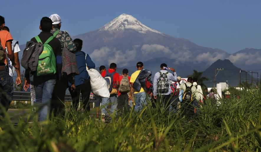Central American migrants begin their morning trek as part of a thousands-strong caravan hoping to reach the U.S. border, as they face the Pico de Orizaba volcano upon departure from Cordoba, Veracruz state, Mexico, Monday, Nov. 5, 2018. A big group of Central Americans pushed on toward Mexico City from a coastal state Monday, planning to exit a part of the country that has long been treacherous for migrants seeking to get to the United States. (AP Photo/Marco Ugarte)