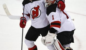 New Jersey Devils goaltender Keith Kinkaid (1) celebrates with Brian Boyle (11), who had a hat trick in an NHL hockey game against the Pittsburgh Penguins in Pittsburgh, Monday, Nov. 5, 2018. The Devils won 5-0. (AP Photo/Gene J. Puskar)