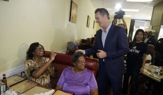 California gubernatorial Democratic candidate Gavin Newsom chats with constituents during a campaign stop at CJ's Cafe, Monday, Nov. 5, 2018, in Los Angeles. (AP Photo/Marcio Jose Sanchez)