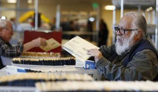 FILE - In this Wednesday, Oct. 31, 2018, file photograph, election judge Thomas Trujillo checks early ballots at the Denver Elections Division headquarters in Denver. (AP Photo/David Zalubowski, File)