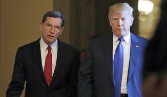 FILE - In this Nov. 28, 2017 file photo, President Donald Trump walks with Sen. John Barrasso, R-Wyo., into a meeting with Senate Republicans on Capitol Hill in Washington. (AP Photo/Alex Brandon, File)