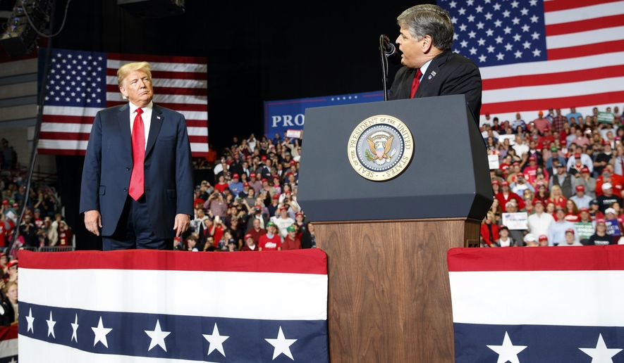 President Donald Trump listens Fox News' Sean Hannity speak during a rally at Show Me Center, Monday, Nov. 5, 2018, in Cape Girardeau, Mo.. (AP Photo/Carolyn Kaster)