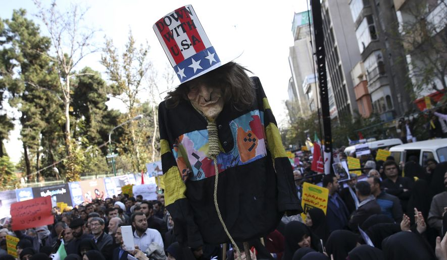 """An effigy of U.S. government icon """"Uncle Sam"""" is held up by demonstrators during a rally in front of the former U.S. Embassy in Tehran, Iran, on Sunday, Nov. 4, 2018, marking the 39th anniversary of the seizure of the embassy by militant Iranian students. Thousands of Iranians rallied in Tehran on Sunday to mark the anniversary as Washington restored all sanctions lifted under the nuclear deal. (AP Photo/Vahid Salemi)"""