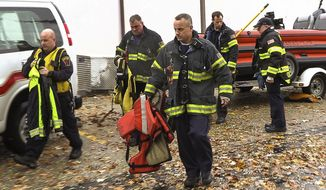 "In this Sunday, Nov. 4, 2018 photo, Skokie and Lake Forest Fire emergency personnel move toward the Lake Front at Highland, Park, Ill. Authorities say a 46-year-old man has died and a 52-year-old woman is missing after going swimming in hazardous waters in Lake Michigan near the Chicago suburb.  The city of Highland Park says in a statement the Elgin woman and the Itasca man were part of a group of people in a ""cold weather swim group"" that went in the lake Sunday morning at Park Avenue Beach amid huge waves and gale-force winds. (Joe Shuman/Chicago Tribune via AP)"