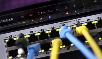 In this June 19, 2018, file photo a router and internet switch are displayed in East Derry, N.H. (AP Photo/Charles Krupa, File)