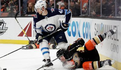 Anaheim Ducks' Ondrej Kase, bottom, of the Czech Republic, falls as Winnipeg Jets' Joel Armia, of Finland, moves the puck during the second period of an NHL hockey game Thursday, Jan. 25, 2018, in Anaheim, Calif. (AP Photo/Jae C. Hong)