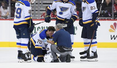 FILE — In this Sept. 30, 2018, file photo, St. Louis Blues center Oskar Sundqvist (70), of Sweden, is tended to by a trainer after he was checked by Washington Capitals right wing Tom Wilson, not seen, during the second period of an NHL preseason hockey game, in Washington. Also seen are Blues defenseman Vince Dunn (29), St. Louis Blues left wing Mackenzie MacEachern (62) and St. Louis Blues right wing Dmitrij Jaskin (23), of Russia. Wilson has been suspended 20 games by the NHL for a blindside hit to the head of an opponent during a preseason game. Wilson's punishment was announced Wednesday, Oct. 3, 2018, just hours before the reigning Stanley Cup champion Capitals were to raise their banner and open their title defense by hosting the Boston Bruins to begin the regular season. (AP Photo/Nick Wass, File) **FILE**