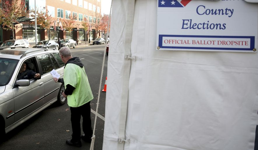 Doug Leaf, a ballot box security guard, grabs ballots from voters at the drive-up drop box in Salem, Ore., on Election Day, Tuesday, Nov. 6, 2018. (Anna Reed/Statesman-Journal via AP) **FILE**