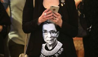 Laura Taylor wears a shirt with a likeness of U.S. Supreme Court justice Ruth Bader Ginsburg as she checks returns at an election night party for Democrats Tuesday, Nov. 6, 2018, in Bellevue, Wash. (AP Photo/Elaine Thompson) **FILE**