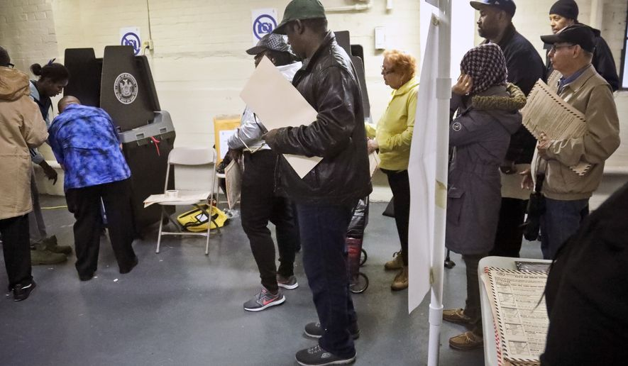 Polling site officials, left, check on a voting scanner after it jammed Tuesday, Nov. 6, 2018, in the Parkchester community of the Bronx borough of New York. The jam forced voters to manually file their ballots until a repair was made. (AP Photo/Bebeto Matthews)