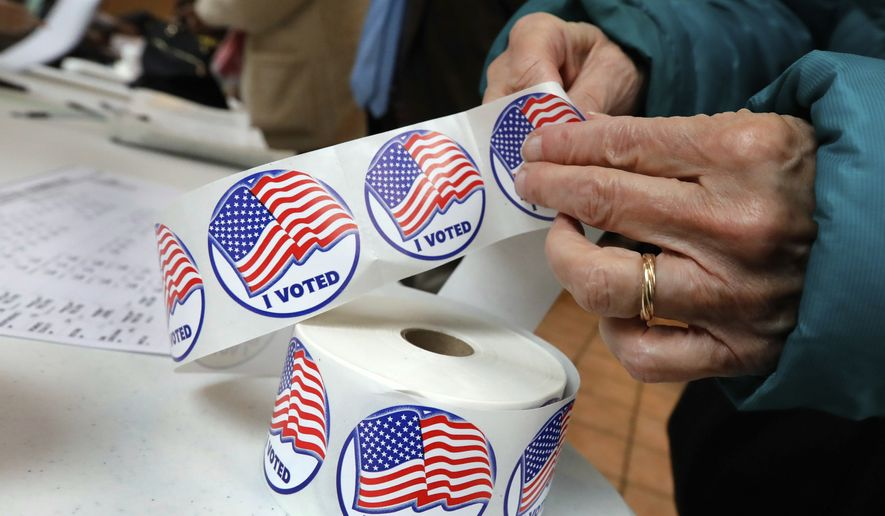 "A voter retrieves her ""I Voted"" sticker after casting her ballot at the Presbyterian Church of Mount Kisco, in Mount Kisco, N.Y. Tuesday, Nov. 6, 2018. (AP Photo/Richard Drew) ** FILE **"