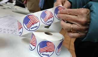 """A voter retrieves her """"I Voted"""" sticker after casting her ballot at the Presbyterian Church of Mount Kisco, in Mt. Kisco, N.Y. Tuesday, Nov. 6, 2018. (AP Photo/Richard Drew)"""