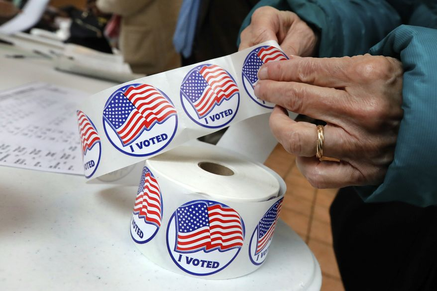 """A voter retrieves her """"I Voted"""" sticker after casting her ballot at the Presbyterian Church of Mount Kisco, in Mount Kisco, N.Y. Tuesday, Nov. 6, 2018. (AP Photo/Richard Drew) ** FILE **"""