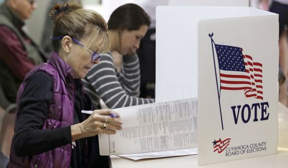 Patricia Wagoner looks over the ballot while voting, Tuesday, Nov. 6, 2018, in Gates Mills, Ohio. Across the country, voters headed to the polls Tuesday in one of the most high-profile midterm elections in years. (AP Photo/Tony Dejak) **FILE**