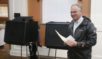 Sen. Tim Kaine, D-Va., carries his ballot to the vote counting machine as he votes in Richmond, Va., Tuesday, Nov. 6, 2018. Kaine is running against Republican Corey Stewart. (AP Photo/Steve Helber)