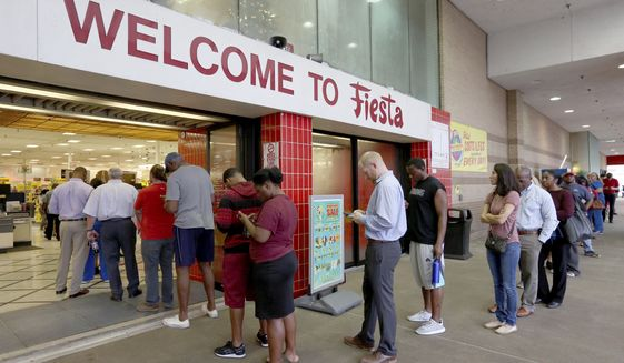Voters line up outside of Fiesta Mart to vote on Election Day, Tuesday, Nov. 6, 2018, in Houston.  (Yi-Chin Lee /Houston Chronicle via AP)