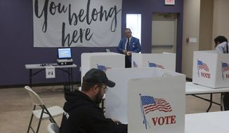 Assistant official of elections Edgar De Leon Izeppi, background, awaits completed ballots at Victory Restoration Church in Christiansburg, Va., Tuesday, Nov. 6 2018. (Matt Gentry/The Roanoke Times via AP)