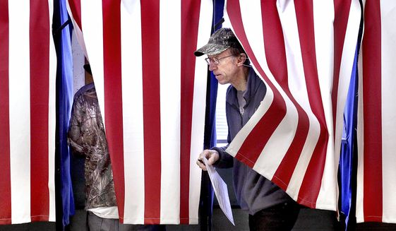 Dan Chase steps out of a voting booth Tuesday, Nov. 6, 2018, at Town of Hamilton Town Hall in West Salem, Wis. (Peter Thomson/La Crosse Tribune via AP)