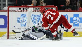 Detroit Red Wings center Dylan Larkin (71) puts his shot past the skate of Vancouver Canucks goaltender Jacob Markstrom (25), of Sweden, during the shootout in overtime of an NHL hockey game Tuesday, Nov. 6, 2018, in Detroit. Larkin's shot won the game 3-2 for the Red Wings. (AP Photo/Duane Burleson)