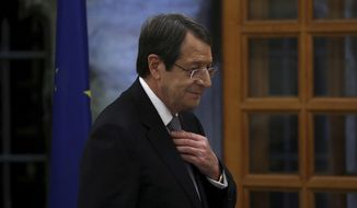 Cyprus' president Nicos Anastasiades adjusts his tie before giving a statement to the media at the presidential palace in divided capital Nicosia, Cyprus, Tuesday, Nov. 6, 2018. Anastasiades holds news conference to elaborate on his vision on how the ethnically split island nation could be reunified as a decentralized federation. (AP Photo/Petros Karadjias)