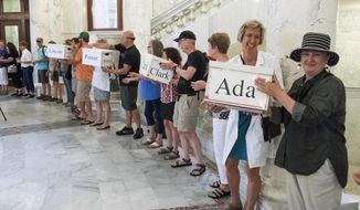 FILE--In this July 6, 2018, file photo, Dr. Kathleen Romito, M.D. hands a box full of signatures from Ada County to Kelly Goughnour, both of Boise, Idaho, at the Idaho Statehouse in Boise, Idaho. In a bucket-brigade-style delivery of more than 70,000 voter petitions from 44 counties, Idahoans For Healthcare volunteers delivered signatures to the Idaho Secretary of State calling for placement of a Medicaid expansion initiative the ballot. Voters will decide Proposition 2's fate Tuesday, Nov. 6, 2018. (Darin Oswald/Idaho Statesman via AP, file)