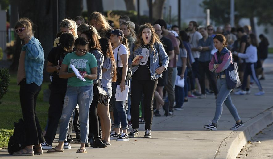 A woman yawns as she waits in a long line to register and vote at the Los Angeles County Registrar's office Tuesday, Nov. 6, 2018, in Los Angeles. A spokesman with the registrar's office says the line at its headquarters in Norwalk is wrapping around the building and that wait times were at about two hours Tuesday. (AP Photo/Mark J. Terrill)