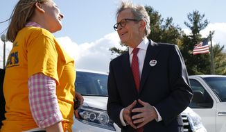 Ohio Republican gubernatorial candidate Mike DeWine, right, greets a voter outside the Green Township Senior Center, a voting precinct, Tuesday, Nov. 6, 2018, in Cincinnati, Ohio. (AP Photo/Gary Landers)