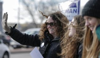 Democratic House candidate Kara Eastman waves to passing motorists in Omaha, Neb., Tuesday, Nov. 6, 2018. Eastman is challenging Nebraska's 2nd District Rep. Don Bacon, R-Neb. (AP Photo/Nati Harnik)