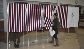 A voter enters a voting booth at Laurel High School on Tuesday, Nov. 6, 2018, in Laurel, Mont. (AP Photo/Matthew Brown) (AP Photo/Matthew Brown)