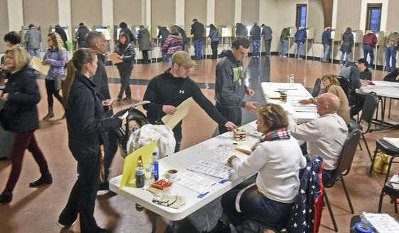 Voters line up to receive ballots while others fill voting booths inside the northwest Bismarck polling place in Century Baptist Church on Tuesday evening. (Tom Stromme/The Bismarck Tribune via AP)