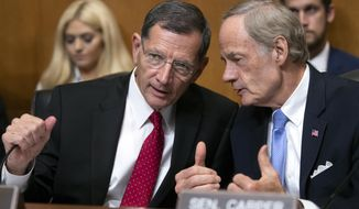 FILE - In this Aug. 1, 2018 file photo, Sen. John Barrasso, R-Wyo., left, chairman of the Senate Environment and Public Works Committee, confers with Sen.Tom Carper, D-Del., the ranking member, on Capitol Hill in Washington. (AP Photo/J. Scott Applewhite, File)