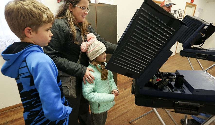 Michael, 10, left, and Addison Nicely, 7, watch as their mother, Melinda, all of Cuba City, Wis., casts her ballot at Smelser Town Hall in Georgetown, Wis., on Tuesday, Nov. 6, 2018. (Nicki Kohl/Telegraph Herald via AP)