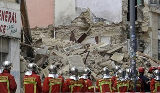 Firefighters work at the scene where a building collapsed In Marseille, southern France, Monday, Nov. 5, 2018. A building collapsed in the southern city of Marseille on Monday, leaving a giant pile of rubble and beams. There was no immediate word on any casualties. (AP Photo/Claude Paris)