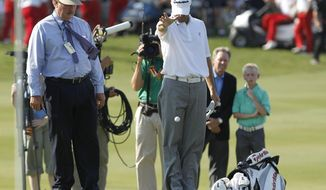 FILE - In  this May 29, 2011, file photo, PGA rules official Slugger White, left, looks on as Ryan Palmer, right, drops his ball after hitting in the hazard during the first playoff hole of the Byron Nelson Championship golf tournament in Irving, Texas. Rules officials around the world have little time to learn a new set of rules effective Jan. 1. (AP Photo/LM Otero, File)