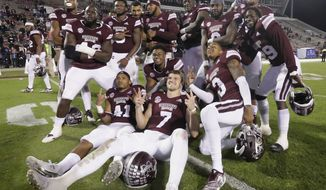 Mississippi State players including front row from left, Mark McLaurin (41), Nick Fitzgerald (7) and Cameron Dantzler (3), pose for a group photo after an NCAA college football game against Louisiana Tech, Saturday, Nov. 3, 2018, in Starkville, Miss. (AP Photo/Jim Lytle)