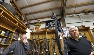 In this Oct. 20, 2017, file photo, sales clerk Tom Wallitner holds up a Mossberg 715T .22-caliber semi-automatic rifle during an auction at Johnny's Auction House, where the company handles gun sales for a half dozen police departments and the Lewis County Sheriff's Office, in Rochester, Wash. The city council in Spokane, Washington, has passed an ordinance prohibiting police from selling confiscated firearms, citing an Associated Press investigation that found that some guns sold by law enforcement were used in new crimes. (AP Photo/Elaine Thompson, File)
