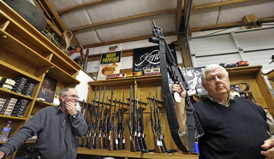 FILE - In this Oct. 20, 2017, file photo, sales clerk Tom Wallitner holds up a Mossberg 715T .22-caliber semi-automatic rifle during an auction at Johnny's Auction House, where the company handles gun sales for a half dozen police departments and the Lewis County Sheriff's Office, in Rochester, Wash. The city council in Spokane, Washington, has passed an ordinance prohibiting police from selling confiscated firearms, citing an Associated Press investigation that found that some guns sold by law enforcement were used in new crimes. (AP Photo/Elaine Thompson, File)