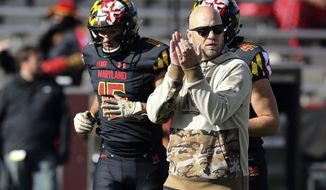 FILE - In this Saturday, Nov. 3, 2018, file photo, Maryland interim head coach Matt Canada, right, watches his team warm up before playing Michigan State in an NCAA college football game in College Park, Md. Canada faces an uncertain future, despite keeping the football team together and forging a winning record amid the chaos surrounding the program. (AP Photo/Gary Cameron) ** FILE **